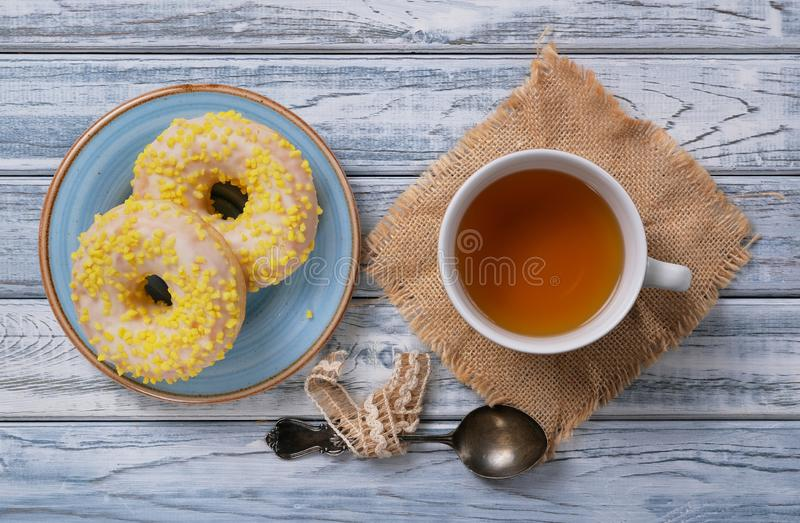 Sweet yellow donuts on a blue glazed saucer and cup of tea royalty free stock images
