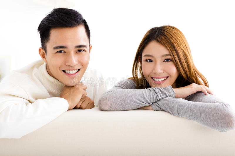 Sweet young couple sitting in sofa stock photography