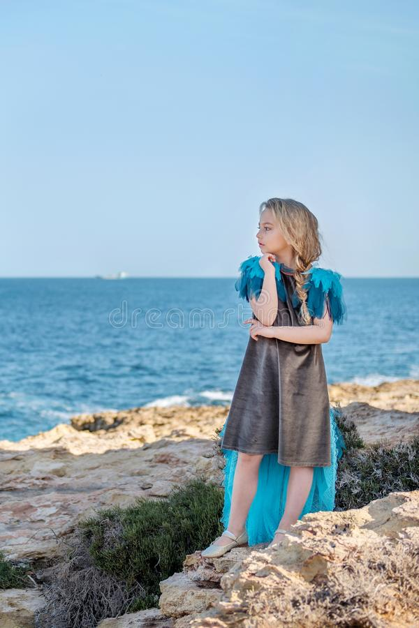 Sweet young girl in azure dress with a tail, like a bird standing on a rocky seashore of the ocean and looking thoughtfully into stock image