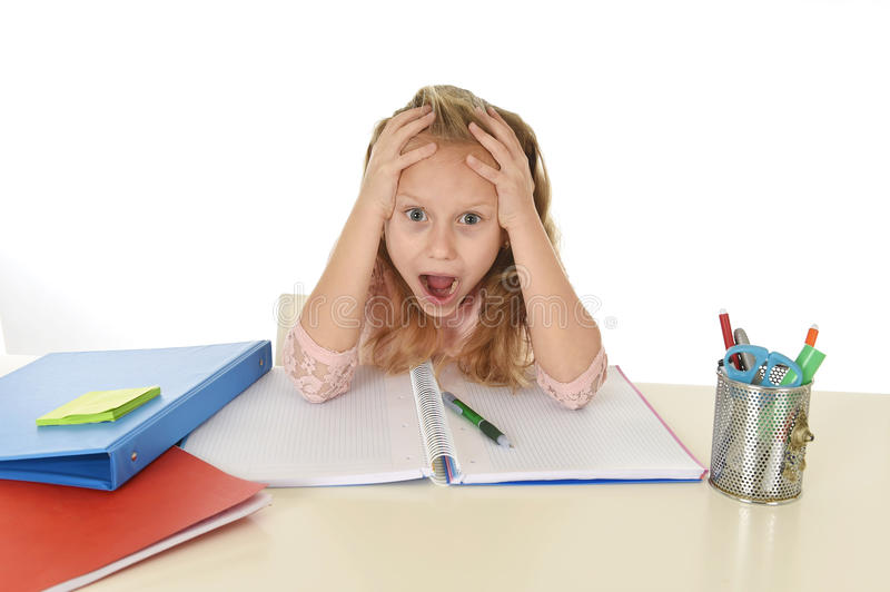 Sweet young little schoolgirl desperate in stress while sitting on school desk doing homework tired. And exhausted screaming crazy isolated on white background royalty free stock photography