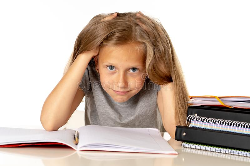 Young girl pulling her hair in stress and over worked education concept. Sweet young little schoolgirl pulling her hair desperate in stress while sitting on royalty free stock photos