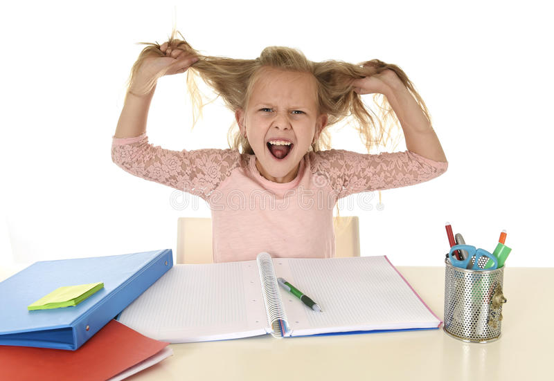 Sweet young little schoolgirl pulling her hair desperate in stress while sitting on school desk doing homework tired. And exhausted screaming crazy isolated on stock photography