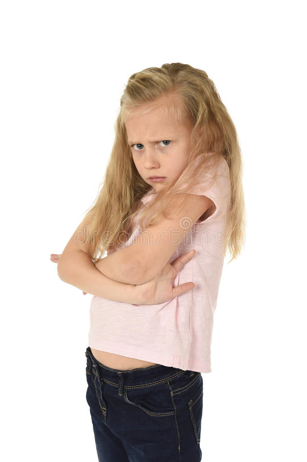 Sweet young schoolgirl with blond hair and folded arms angry upset frustrated and unhappy. Cute and sweet young schoolgirl with blond hair and folded arms royalty free stock photography