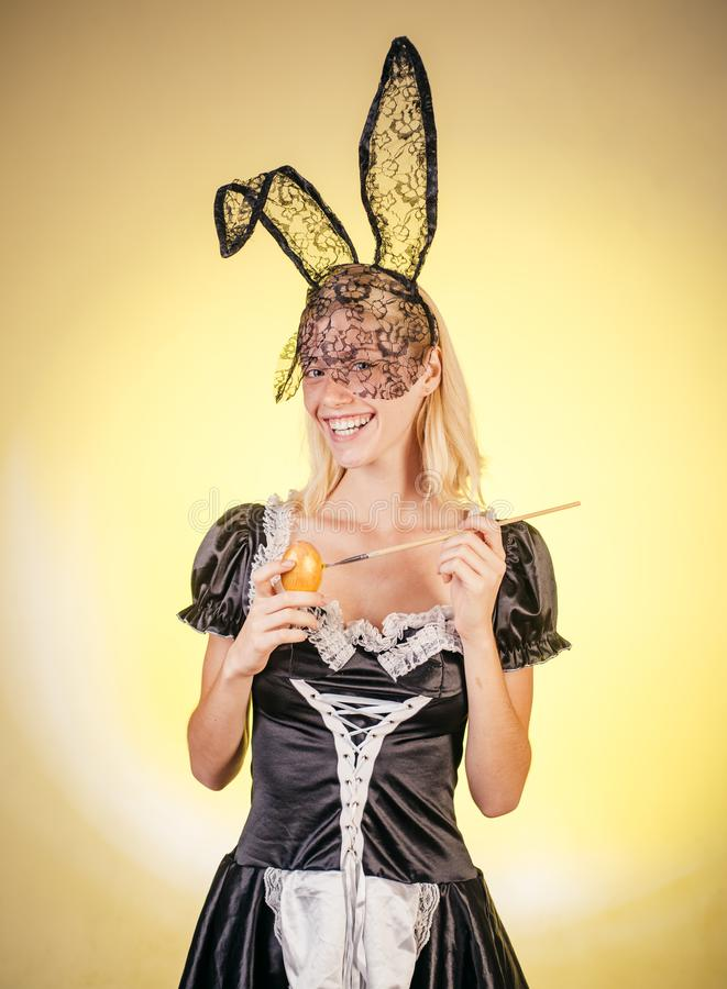 Sweet young woman painting eggs, copy space. Crazy people. Easter eggs. A beautiful sensual blonde depicts an Easter egg stock image