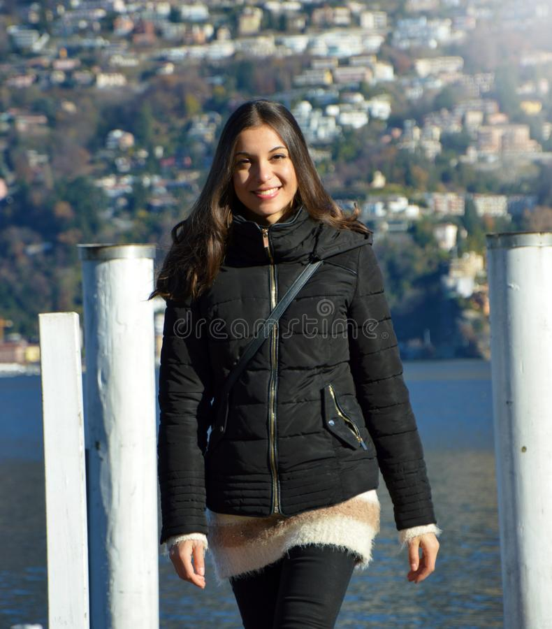 Sweet young woman with winter clothes walking on pier gangway of Lake Lugano with mountains on the background and flare sun light, stock image
