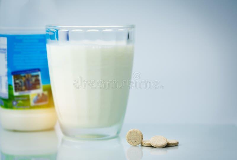 Sweetened flavored tabuletas do leite e um vidro do leite e da garrafa de leite no fundo branco Produtos alimentares do cálcio do imagens de stock