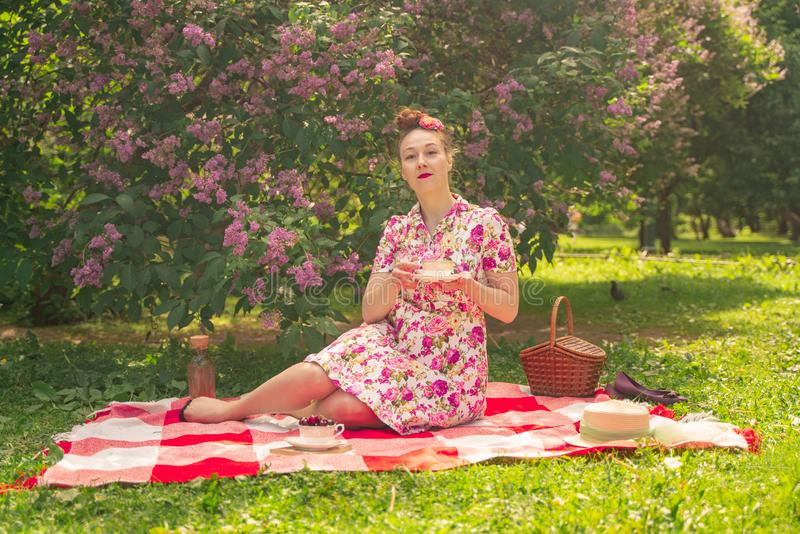 Sweetheart charming pinup girl in a summer dress on a checkered blanket in the Park near the bushes of lilac enjoys life and leisu royalty free stock photos