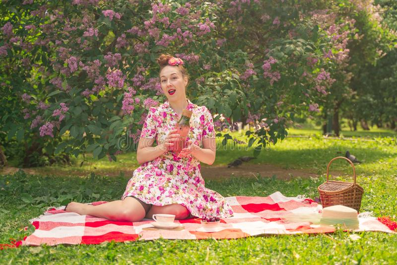 Sweetheart charming pinup girl in a summer dress on a checkered blanket in the Park near the bushes of lilac enjoys life and leisu stock photos