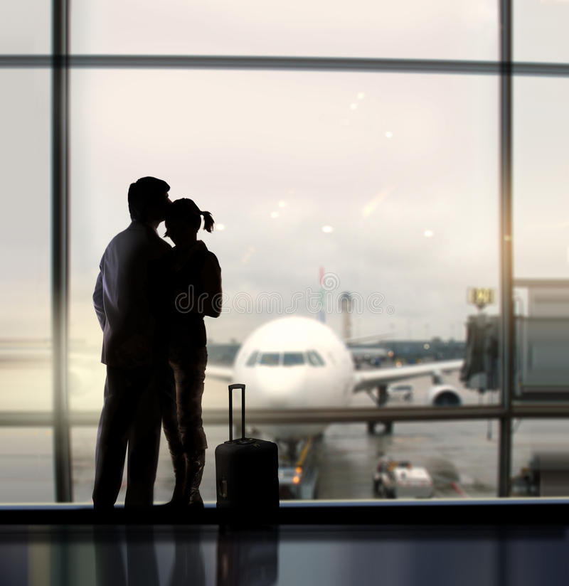 Sweethearts in airport. Silhouette of pair of lovers near the window in airport