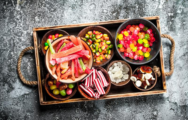 Sweets candy, candied fruits with marshmallow and jelly on a wooden tray. On a rustic background royalty free stock photo