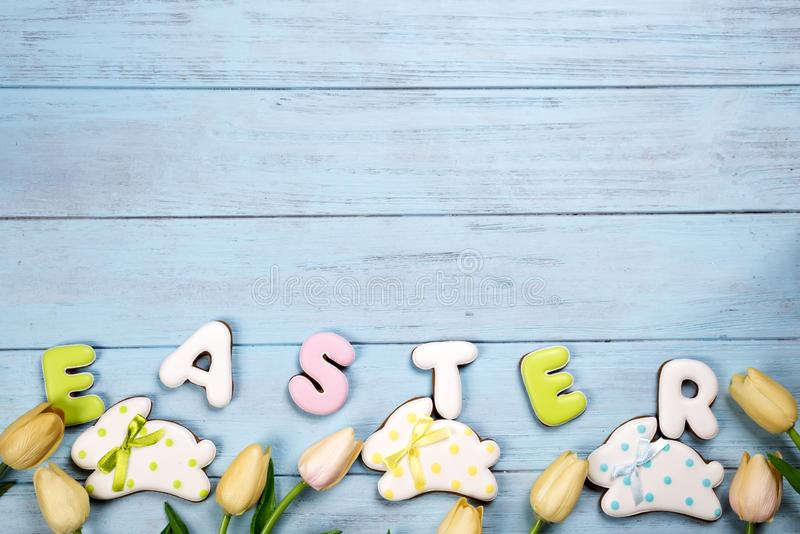 Sweets for celebrate Easter. Gingerbread in shape of easter bunny and letter Easter, tulips stock photos