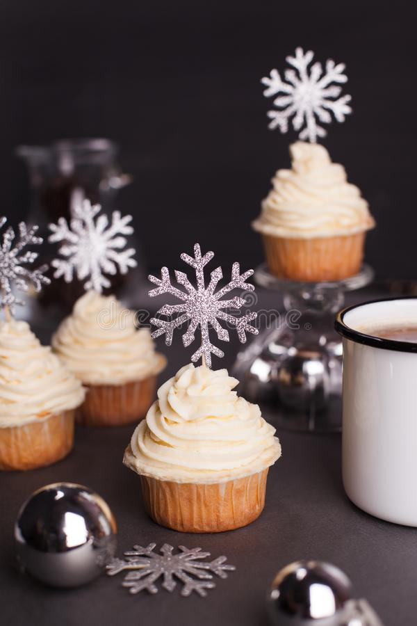 Set of winter Christmas New Year cup cakes on black background. Sweets for christmas - Christmas cupcake with cream cheese decorated with shining silver royalty free stock photo