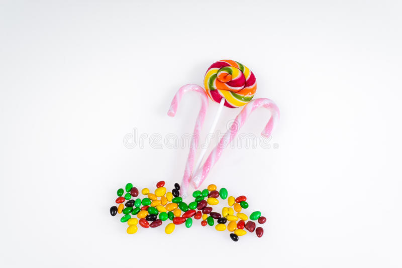 Sweets - colored lollipop and pink with white stripes stick on a white background. Sweets - colored lollipop and pink with white stripes stick on a white royalty free stock photo