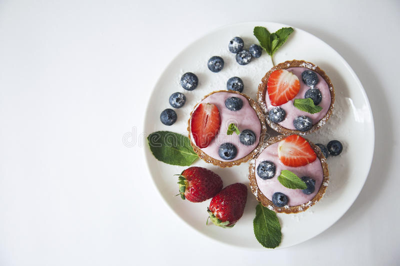 Sweets with cream and strawberries stock photography