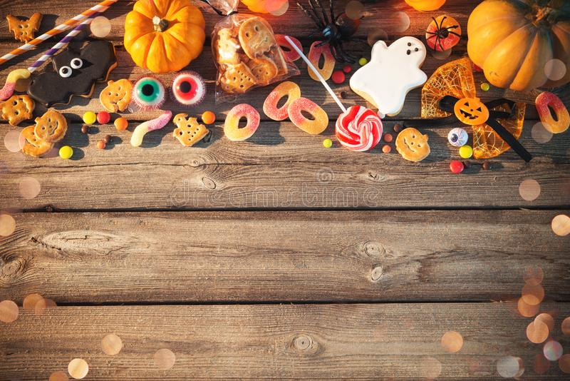 Sweets for Halloween. Trick or treat. Sweets for Halloween and fresh pumpkin on wooden table with copy space. Trick or treat stock photography