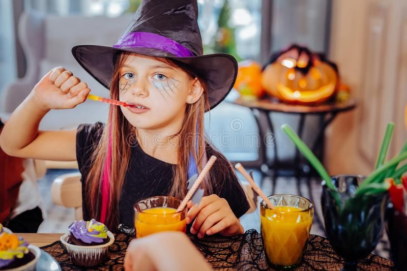 Cute girl wearing wizard Halloween suit enjoying thematic sweets and juice royalty free stock photo