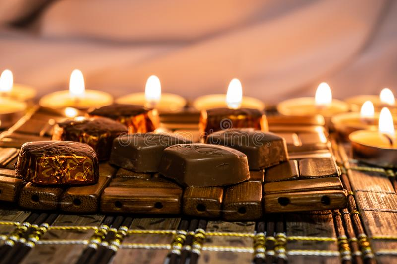 Sweets, milk candies and dark chocolate broken, on the background of lights, candles. Warm, soft and pleasant shade. Dessert is gentle and natural in a stock photos