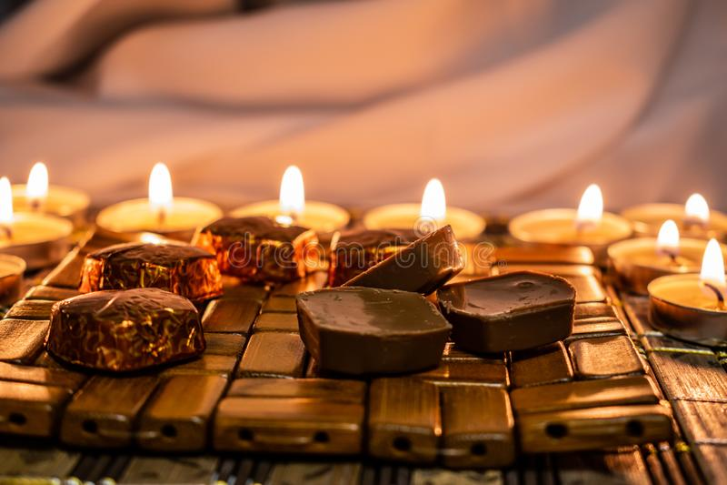 Sweets, milk candies and dark chocolate broken, on the background of lights, candles. Warm, soft and pleasant shade. Dessert is gentle and natural in a royalty free stock photos