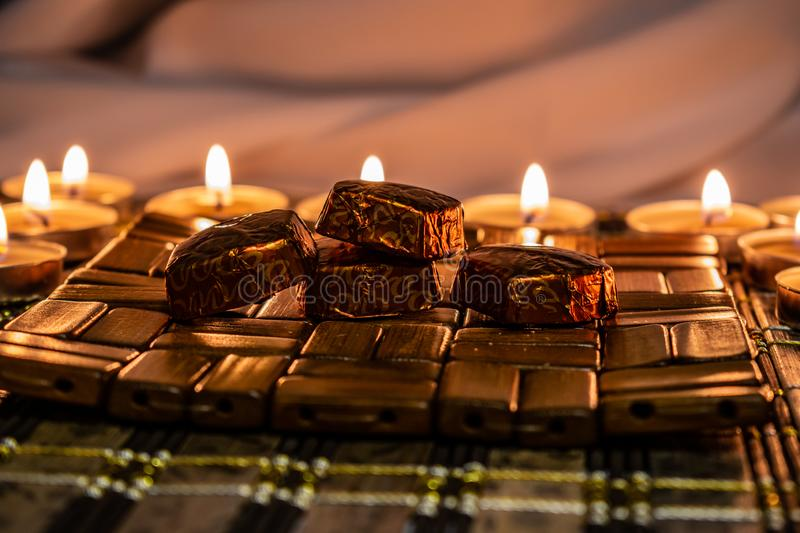 Sweets, milk candies and dark chocolate broken, on the background of lights, candles. Warm, soft and pleasant shade. Dessert is gentle and natural in a royalty free stock photography