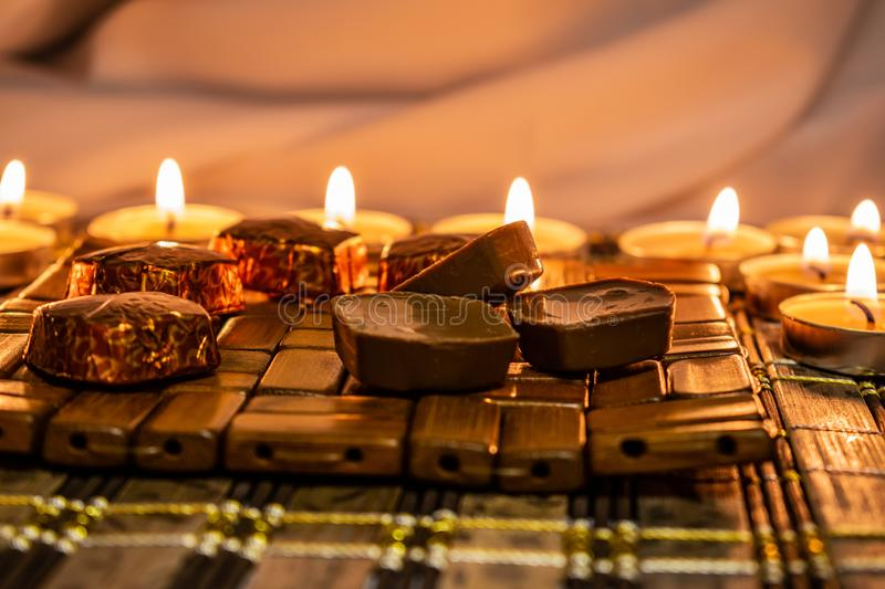 Sweets, milk candies and dark chocolate broken, on the background of lights, candles. Warm, soft and pleasant shade. Dessert is gentle and natural in a royalty free stock images