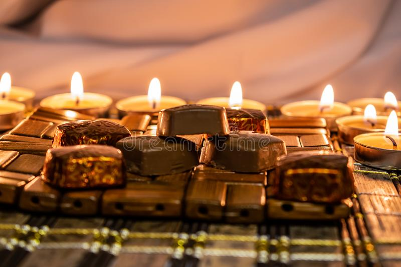 Sweets, milk candies and dark chocolate broken, on the background of lights, candles. Warm, soft and pleasant shade. Dessert is gentle and natural in a royalty free stock image