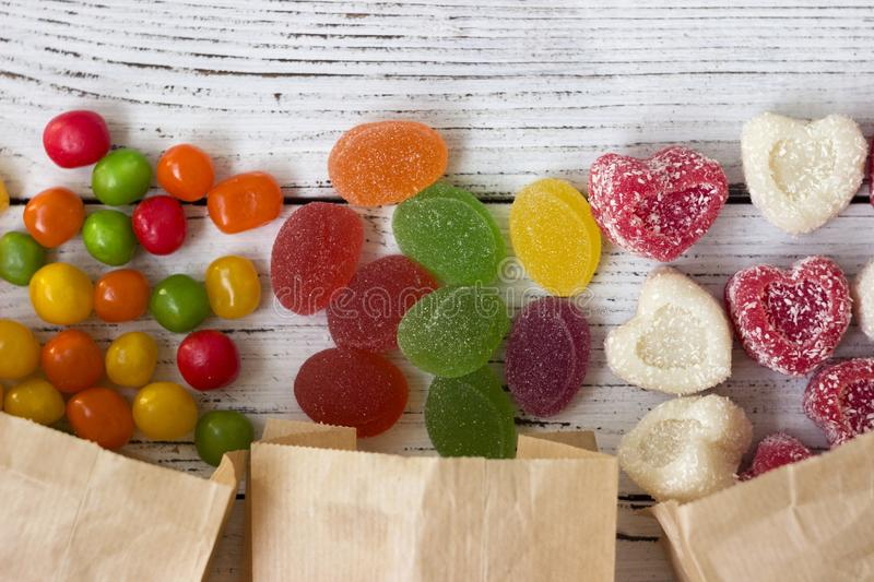 Sweets in paper bags. Multicolored candy, marmalade in the form of heart stock images