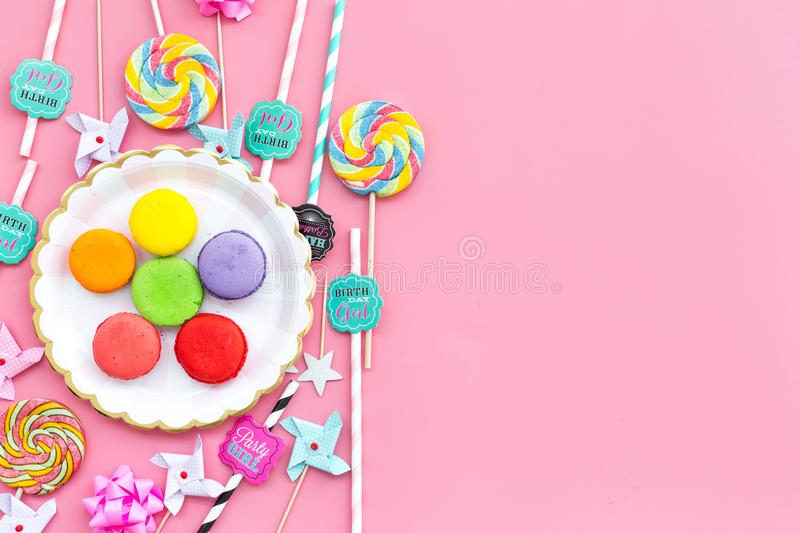 Sweets for party background. Macarons and lollipop on pink top view copy space stock photography