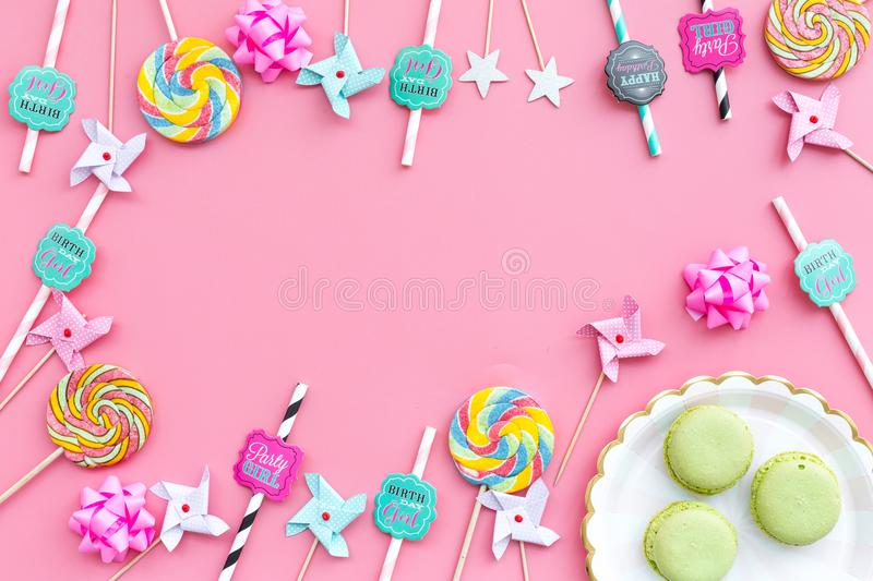 Sweets for party background. Macarons and lollipop on pink top view copy space stock images