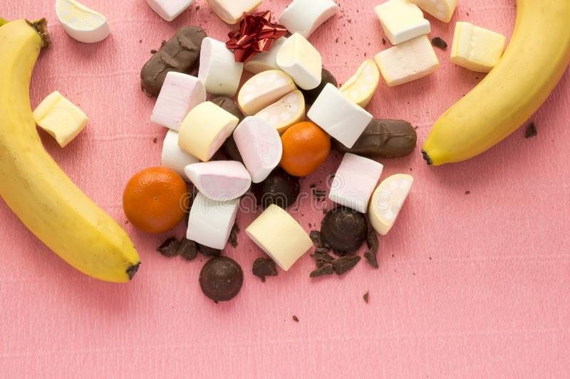 Sweets on pink background with copy space. Delicious chocolates candies, homemade marshmallow zephyr, banana and royalty free stock images