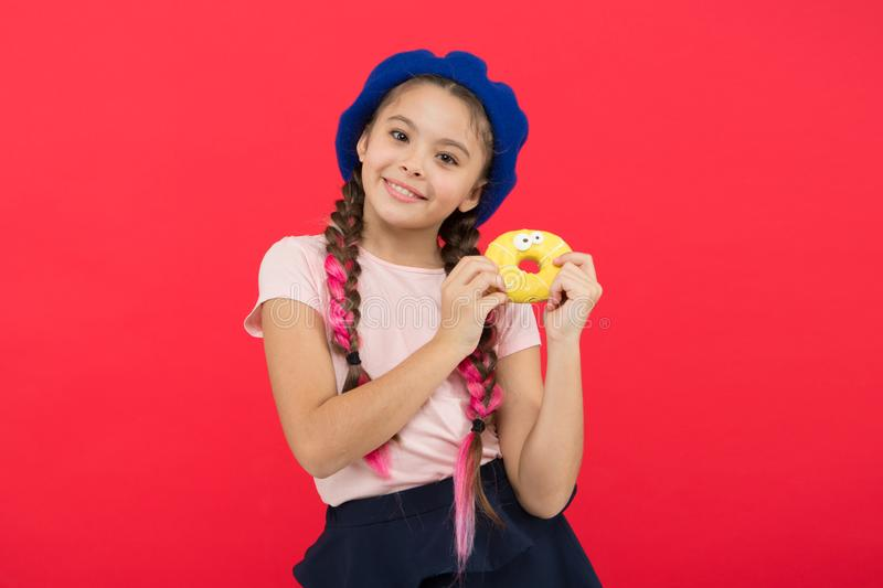 Sweets shop and bakery concept. Kid fan of baked donuts. Delicious sweet donut. Girl in beret hat hold donut red. Background. Kid playful girl eat donut. Health stock photos
