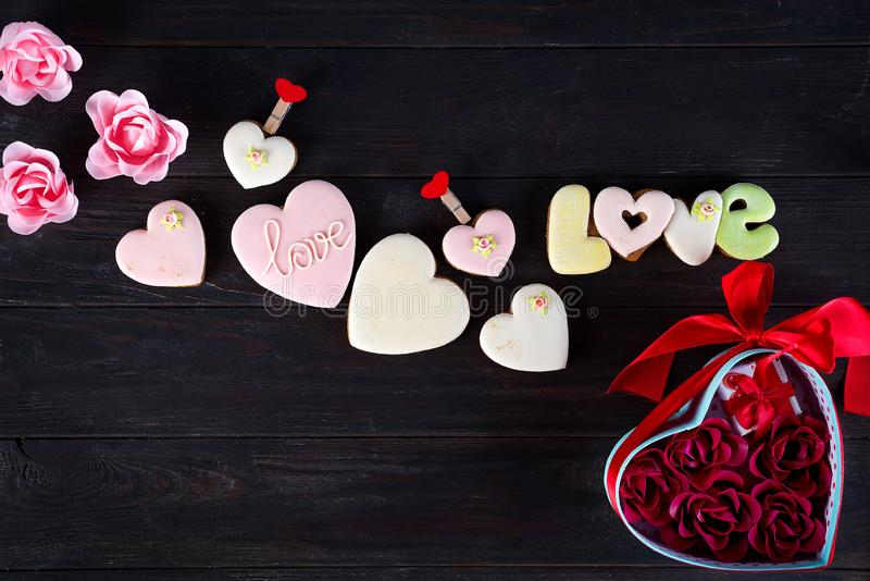 Sweets on Valentine`s Day. Cookies in shape of heart and lettering Love, red hearts shaped and bouquet rose in gift box stock image