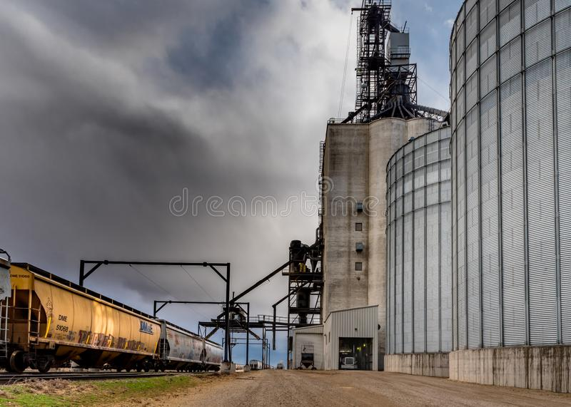 Swift Current, SK/Canada- 10 May, 2019:  Semi unloading with stormy skies at Paterson Grain Terminal in Swift Current, SK, Canada. Swift Current, SK/Canada- 10 royalty free stock photo