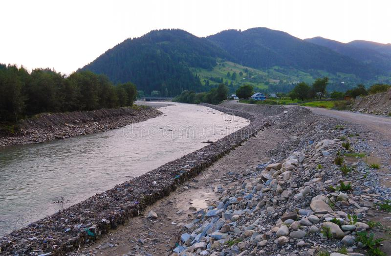 A swift mountain river with stone banks on both sides against the background of a high green mountain. For your design stock image
