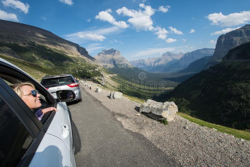 SWIFTCURRENT, LA TA : La femelle blonde admire le beau paysage de montagne le long d'aller à la route de Sun au Montana de photo libre de droits