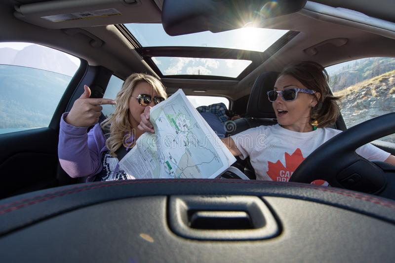 Two female travelers on a road trip struggle with reading a map, looking lost, along Going to the stock photography