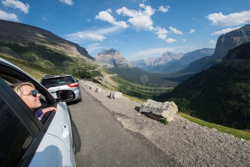 SWIFTCURRENT, TA: A fêmea loura admira o cenário bonito da montanha ao longo de ir à estrada de Sun em Montana de foto de stock royalty free