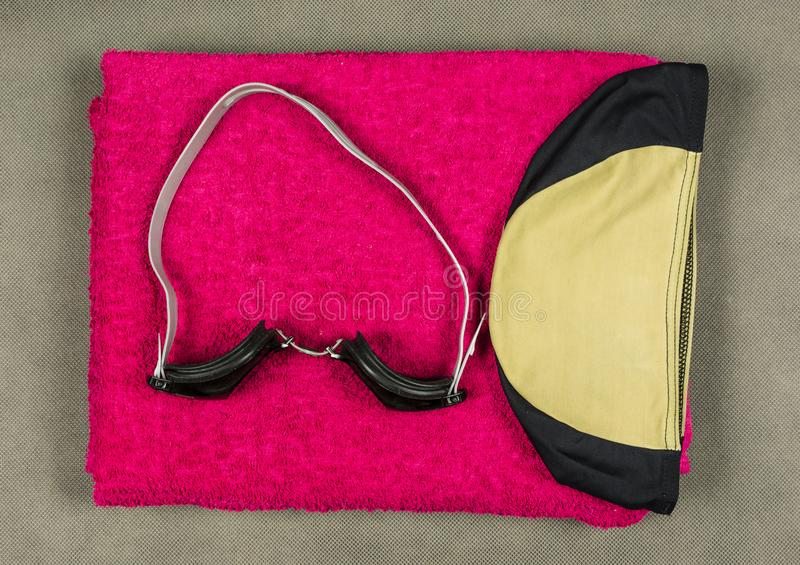 Swim cap, swimming goggles and towel. That is, equipment for a swimmer stock photo