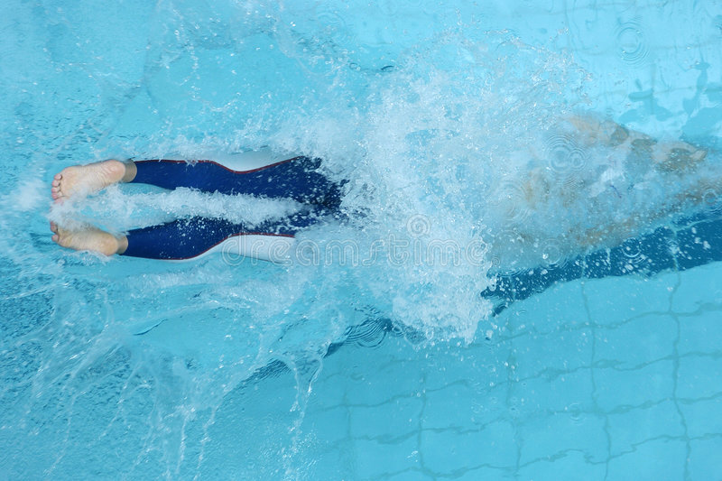 Swim dive 01. A swimmer dives into the water at the start of a race royalty free stock photography