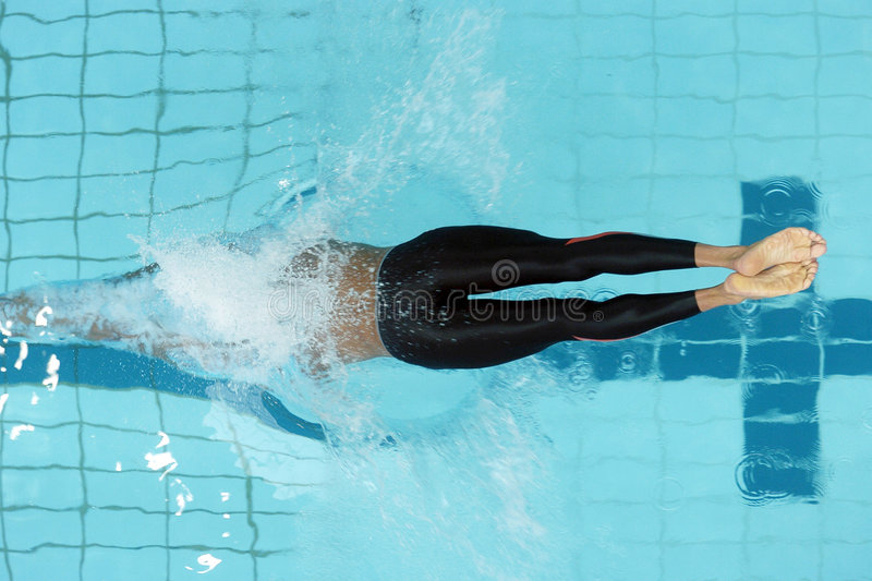 Swim start 01. A male swimmer dives from the start into the pool royalty free stock photo