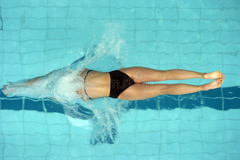Swim start 02. A woman swimmer dives into the pool from the start of a race royalty free stock image