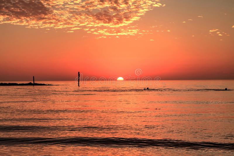 Swim at sunset with a red sky over South Marco Island Beach stock photos