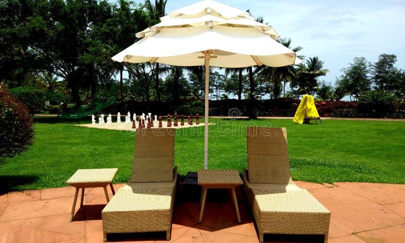 Swimingpool dagdrivare och paraply på golv Begreppet f?r vilar, avkoppling, ferier, brunnsorten, semesterort fotografering för bildbyråer