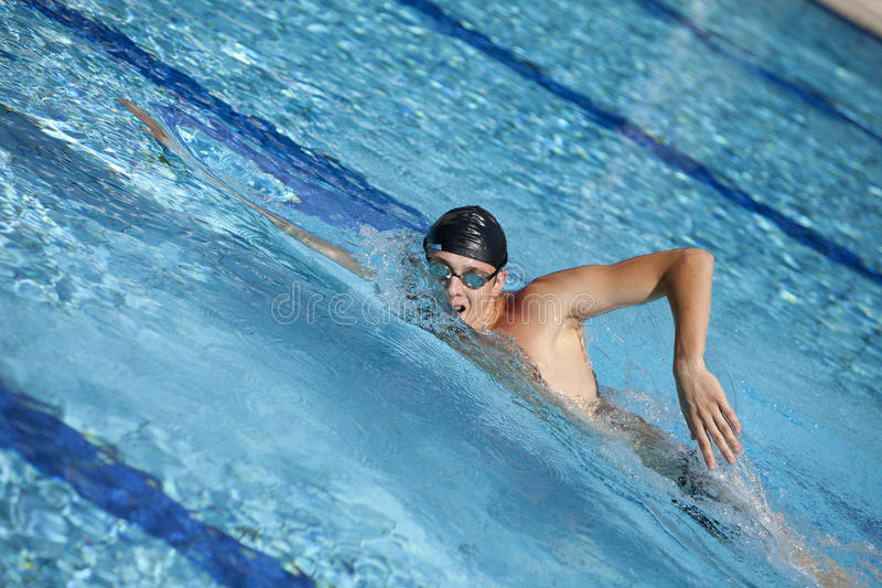 Swimmer in cap breathing during front crawl. In swimming pool stock photo