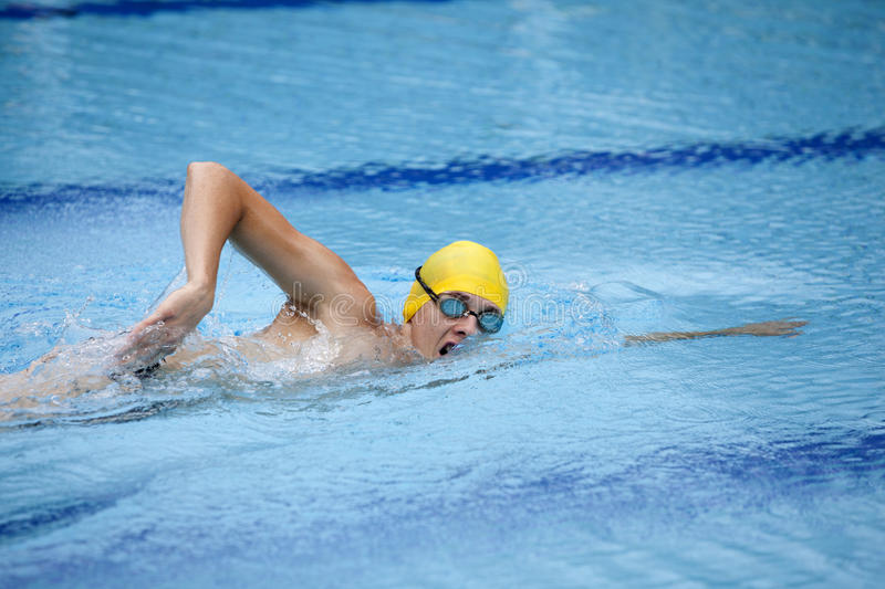 Swimmer in cap breathing during front crawl. Swimmer in yellow cap breathing during front crawl royalty free stock photography