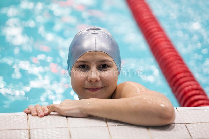 Swimmer girl holding board in swimming pool, young sportsman on the workout royalty free stock photo