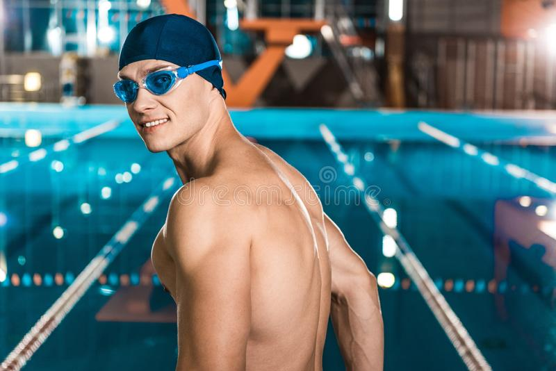 Swimmer. Handsome muscular swimmer in swimming cap and goggles stock photo