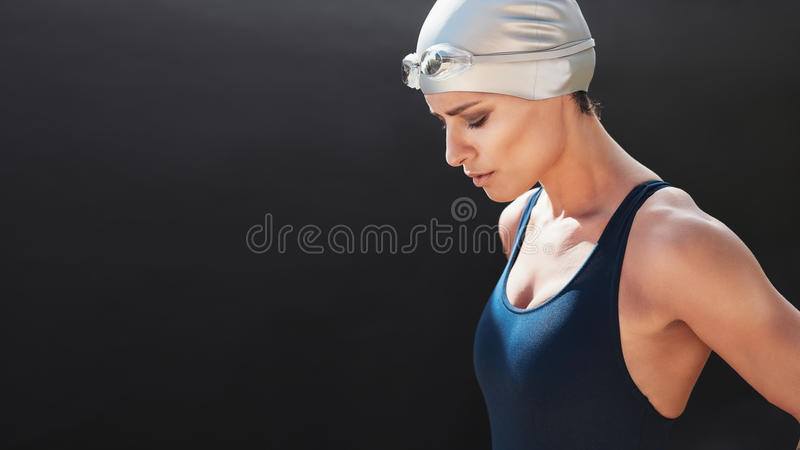 Swimmer preparing for a swim. Portrait of young female swimmer concentrating on black background. Young woman in swimsuit with copy space royalty free stock image