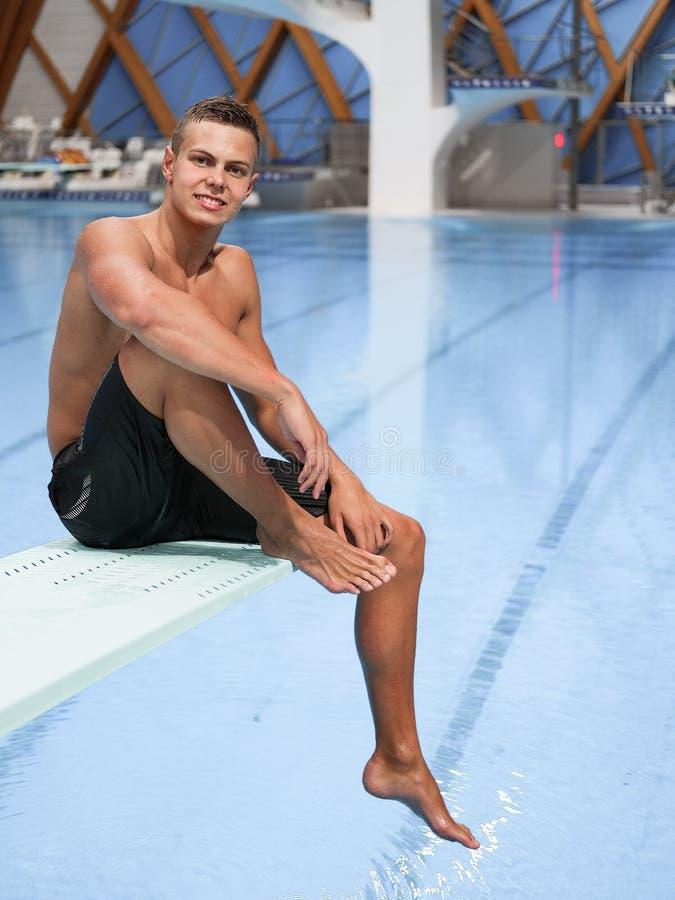 Swimmer se senta em uma plataforma para mergulho imagens de stock