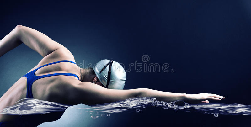 Swimmer swims. Swimmer swims crawl style on a dark background royalty free stock photos