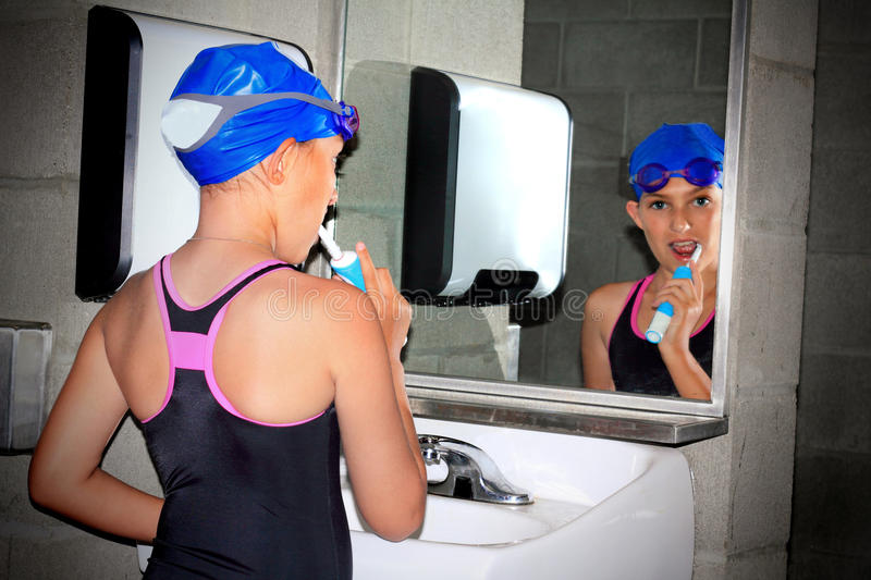 Swimmer tween brushing teeth. A closeup of a little preteen girl wearing swim suit and swim gear brushing her teeth while looking in a bathroom mirror. Shallow stock images